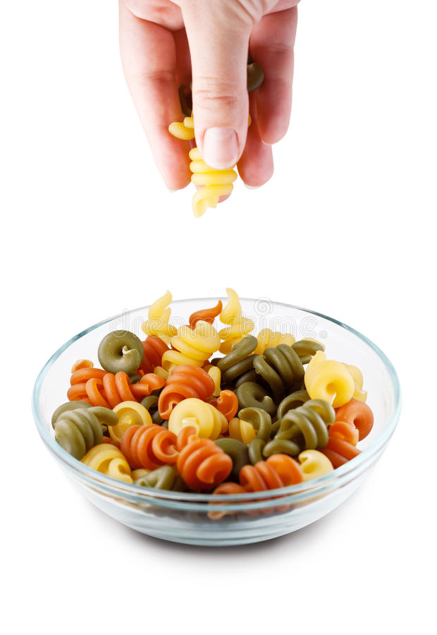 Picking trottole pasta out of bowl, clipping path royalty free stock photos