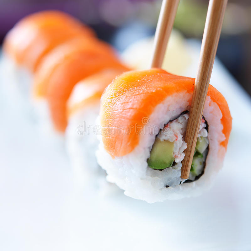 Picking up a piece of sushi with chopsticks. Picking up a piece of salmon sushi with chopsticks, shot with selective focus stock photography