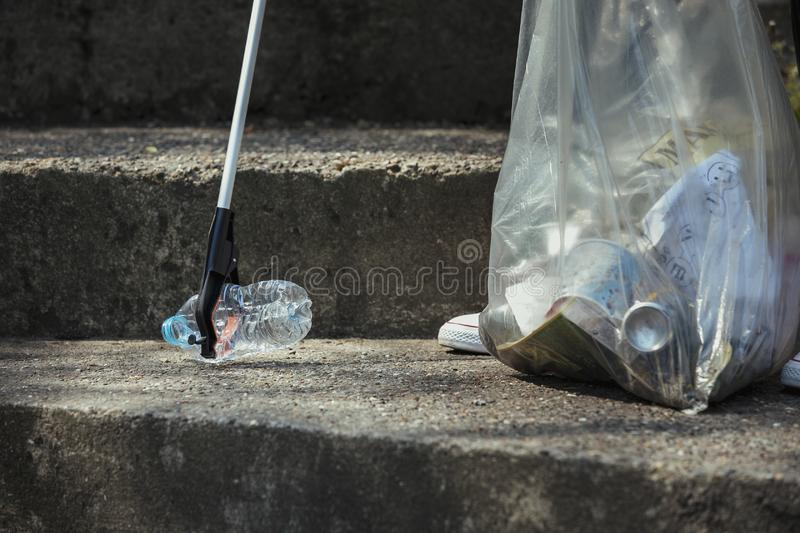 Picking Up a Plastic Bottle. A close-up of an unrecognizable person picking up a plastic bottle on the streets royalty free stock photo