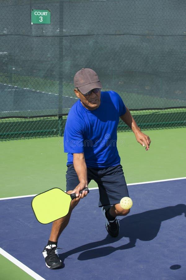 Pickleball行动-蓝色击中的正手击球的人在边线附近 库存图片