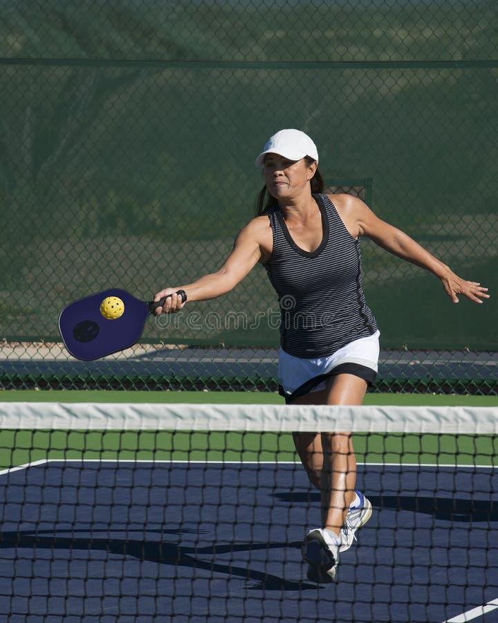 Pickleball -击中正手击球的女性球员 免版税库存照片