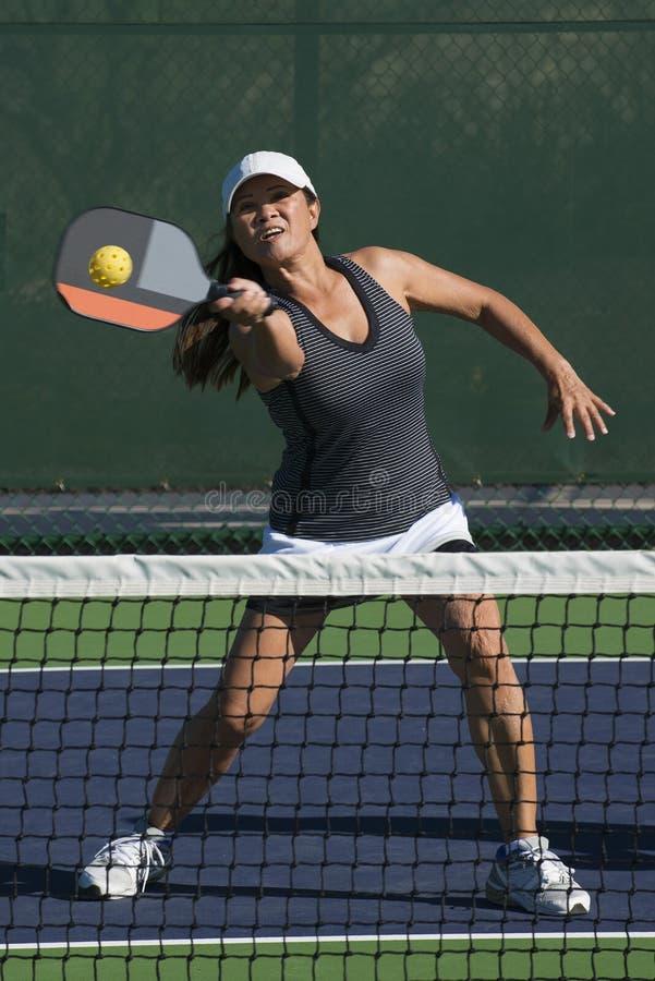 Pickleball -击中正手击球的女性球员 免版税图库摄影