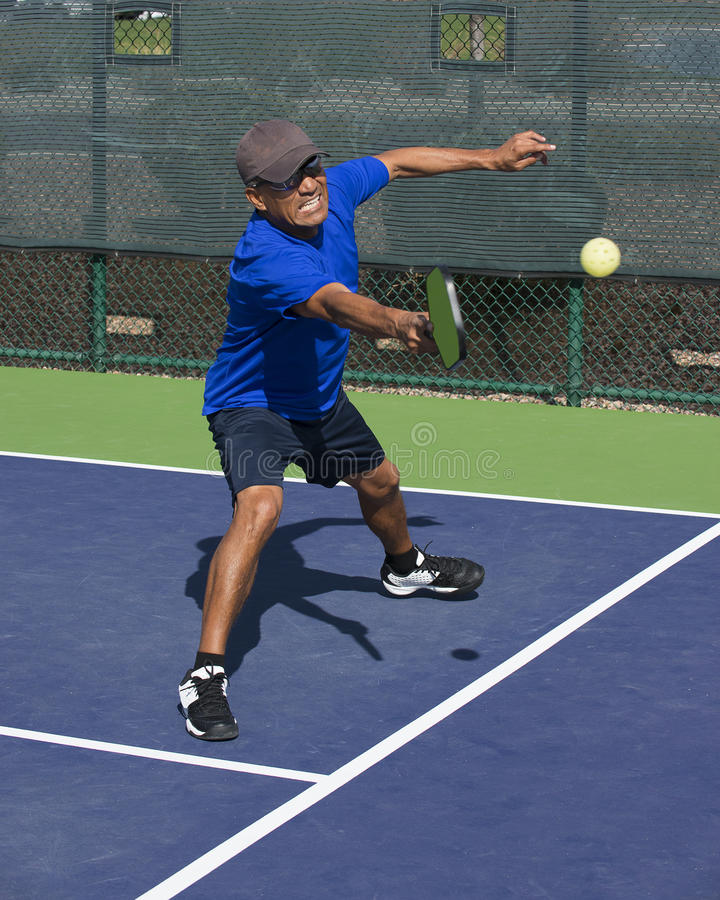 Pickleball Action - Man Wearing Blue Gritting Teeth While Stretching To Hit Forehand Shot. Colorful action image of pickleball player with intense expression on stock photo