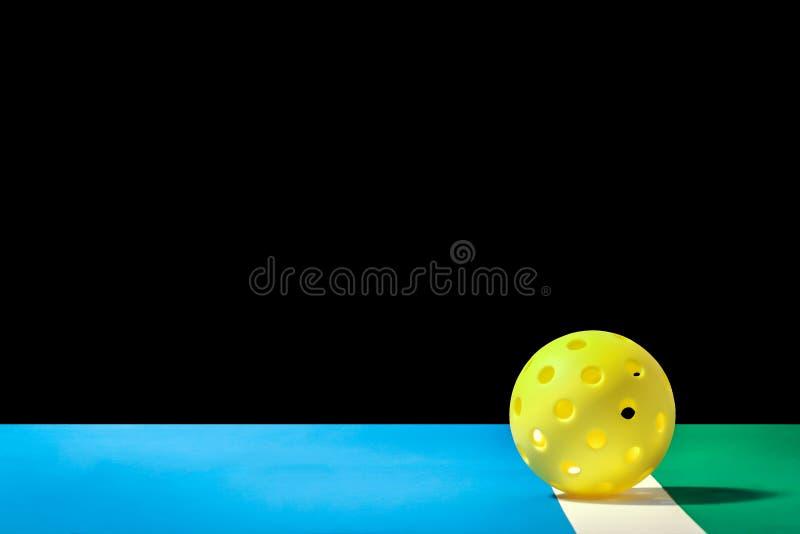 Pickleball amarelo pequeno com grande fundo fotografia de stock royalty free