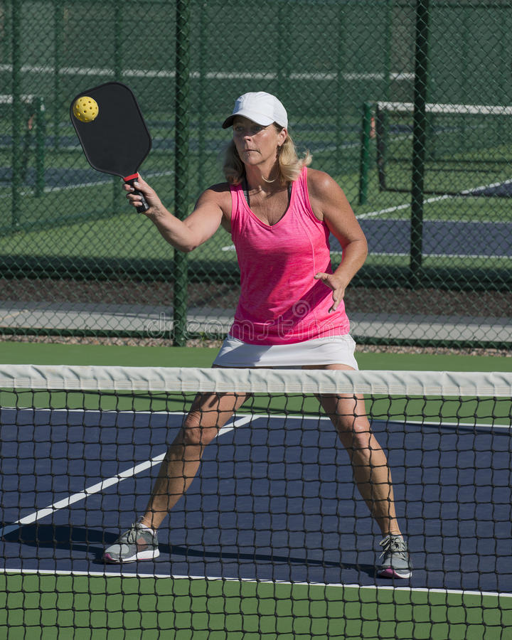 Pickleball - bola de golpe femenina en la red foto de archivo