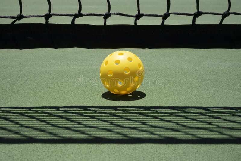 Pickleball On Court Near Net with Shadows stock photography