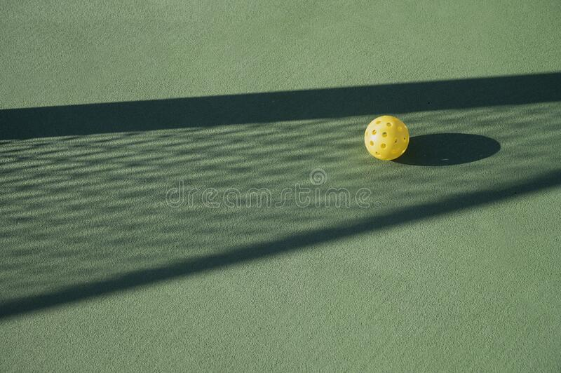 Pickleball on Court in Net Shadow royalty free stock photography