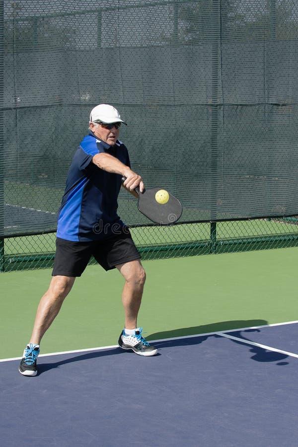 Pickleball handling - hög man som går en serve med en backhand- slaglängd tillbaka royaltyfri foto
