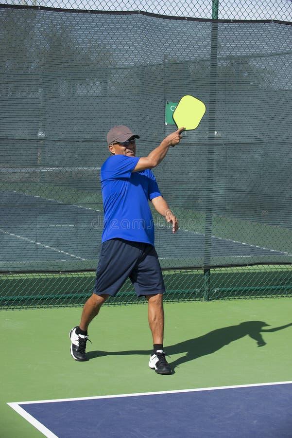 Pickleball-Macher in blauem durch folgen, nachdem der Ball gedient worden ist lizenzfreie stockfotografie