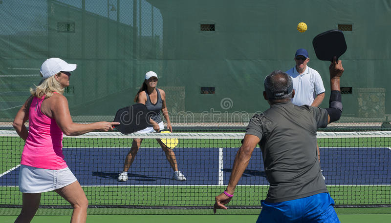 Pickleball - Mixed Doubles Action. Colorful action image of mixed doubles team during a pickleball game royalty free stock photography