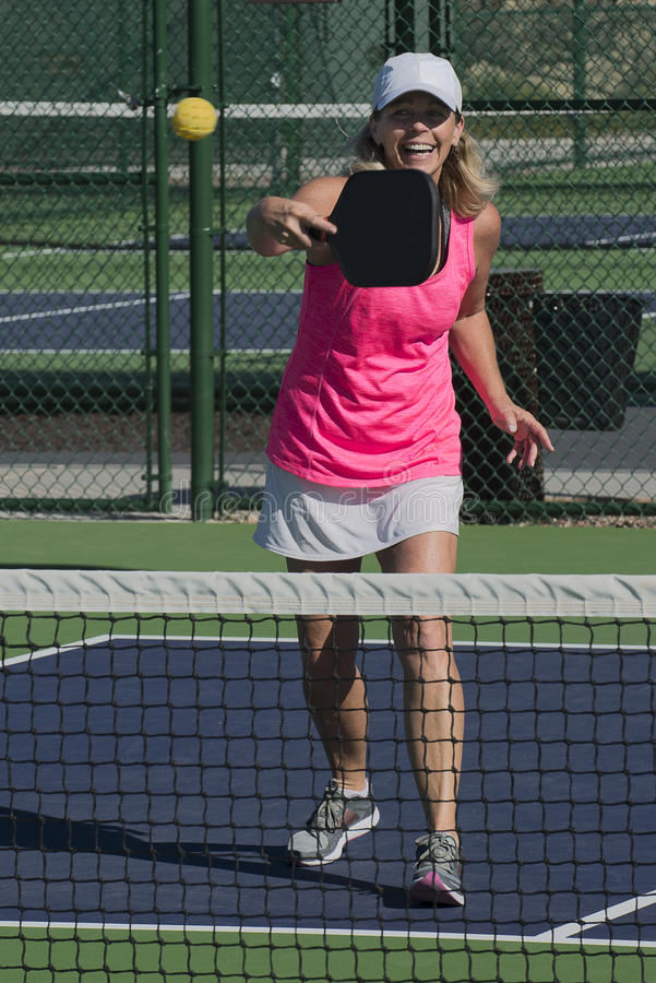 Pickleball - Smiling Female Hitting Ball At Net royalty free stock image