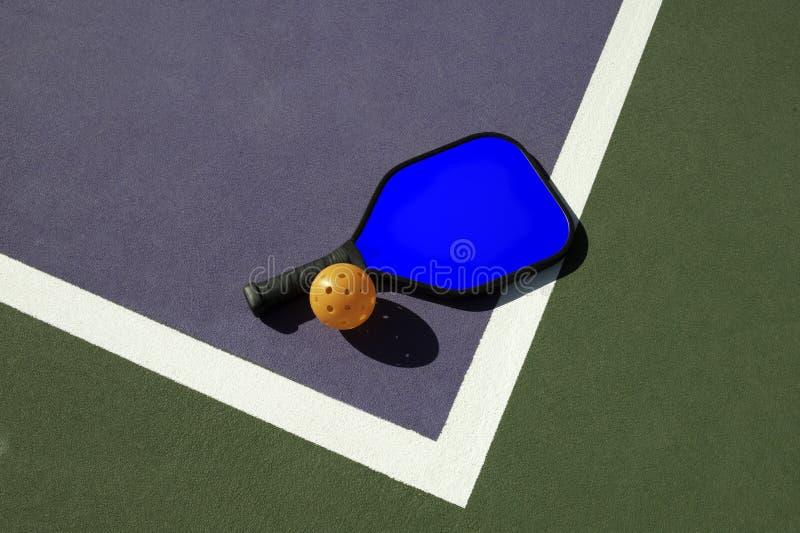 Pickleball y paleta azul en el borde de la corte fotografía de archivo