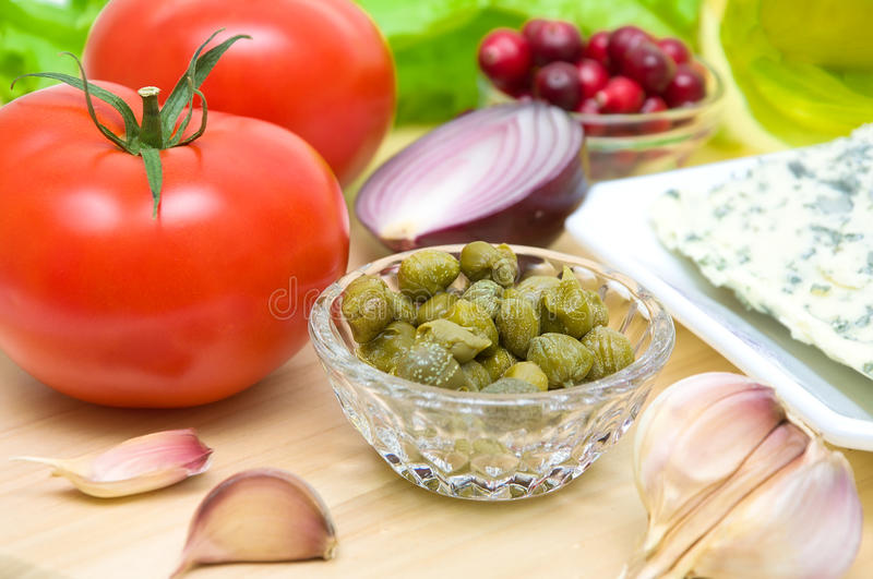 Pickled capers, vegetables, cheese and cranberries on a cutting stock photos