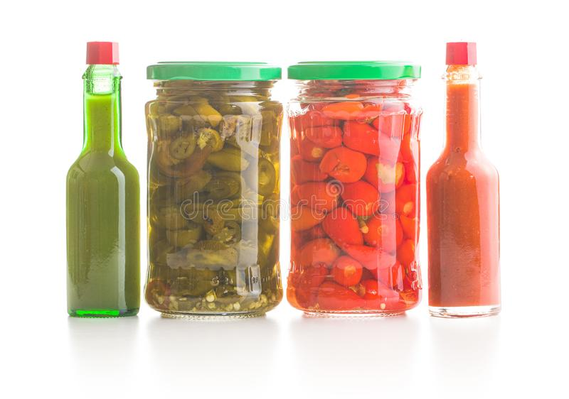 Pickled chili peppers and jalapeno peppers stock photos