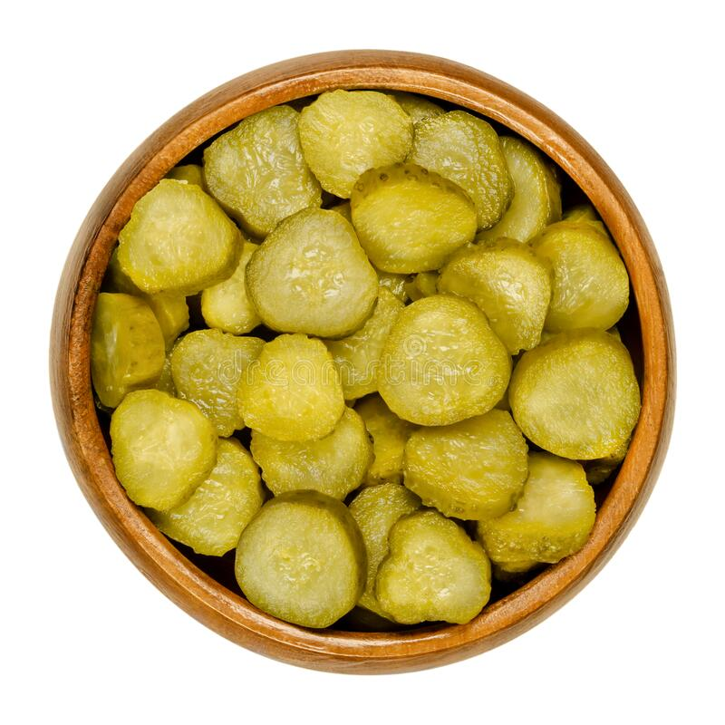 Pickled cucumber discs, known as pickle or gherkin, in wooden bowl stock images