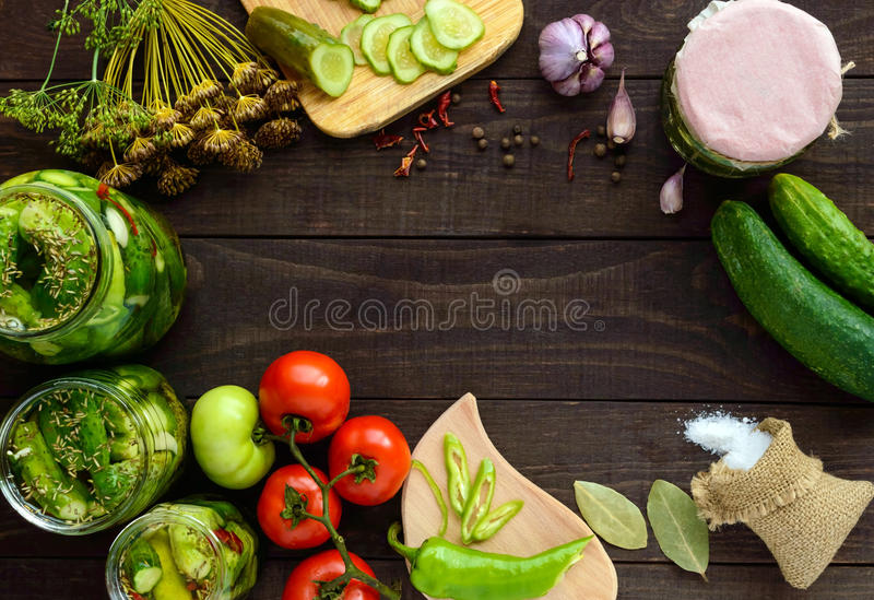 Pickled cucumbers in glass jars. Spices and vegetables for preparation of pickles. stock image
