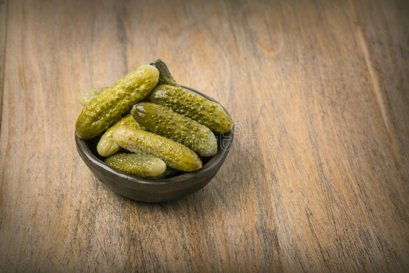 Pickled cucumbers in a wooden bowl stock images
