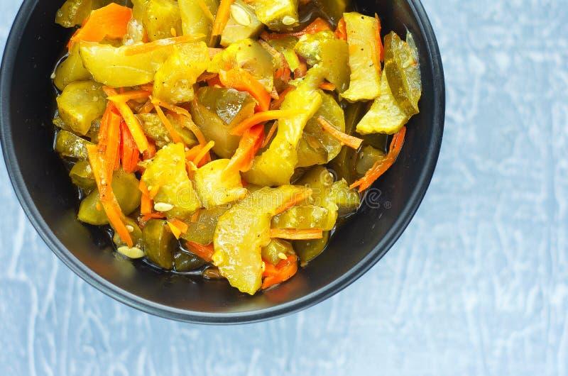 Pickled fermentó los pepinos y las zanahorias en un cuenco de ensalada oscuro Visión superior imagen de archivo