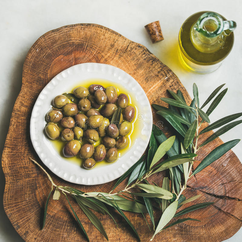 Pickled green Medoterranean olives and olive-tree branch on wooden board royalty free stock photos