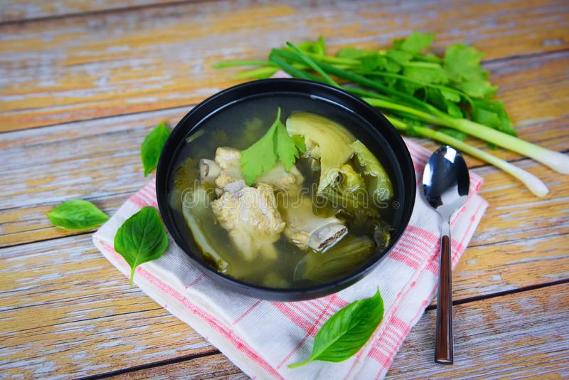 Pickled lettuce soup with spare ribs pork bone soup bowl with vegetable on wood table royalty free stock image