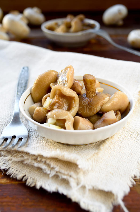 Pickled mushrooms with garlic in white bowl. On wooden background stock image