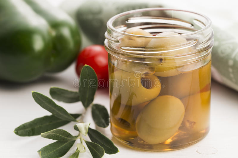 Pickled olives and olive branch royalty free stock image