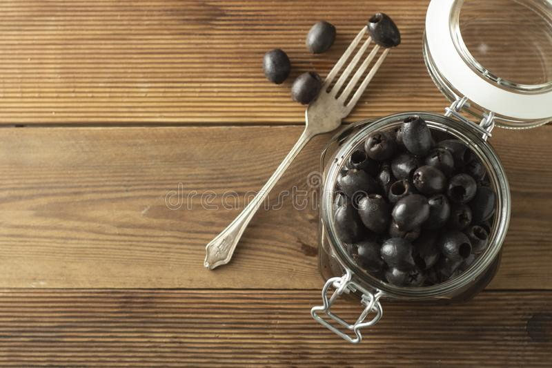 Pickled pitted black olives in glass jar, wooden background. Mediteranian foods. Copy space. Pickled pitted black olives in glass jar, wooden background royalty free stock image