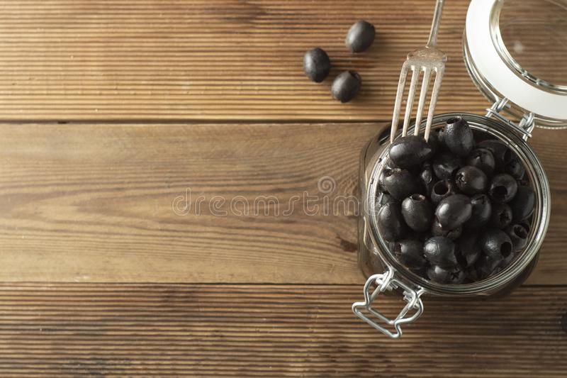 Pickled pitted black olives in glass jar, wooden background. Mediteranian foods. Copy space. Pickled pitted black olives in glass jar, wooden background royalty free stock photography