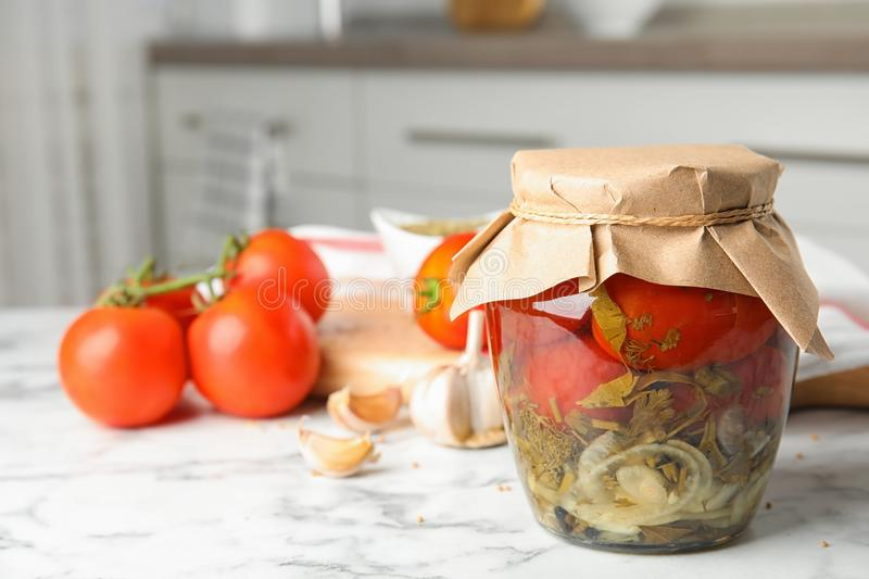 Pickled tomatoes in glass jar and  on white marble table in kitchen. Pickled tomatoes in glass jar and products on white marble table in kitchen royalty free stock photography