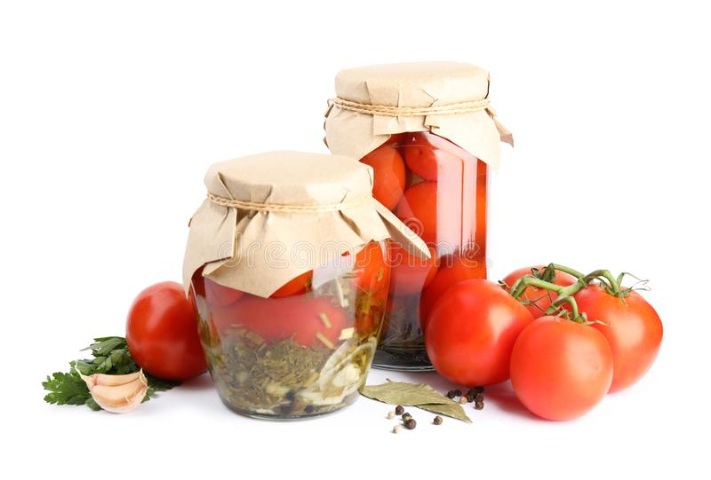 Pickled tomatoes in glass jars and products stock photos