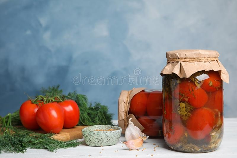 Pickled tomatoes in glass jars and products on white wooden table against blue background stock photography