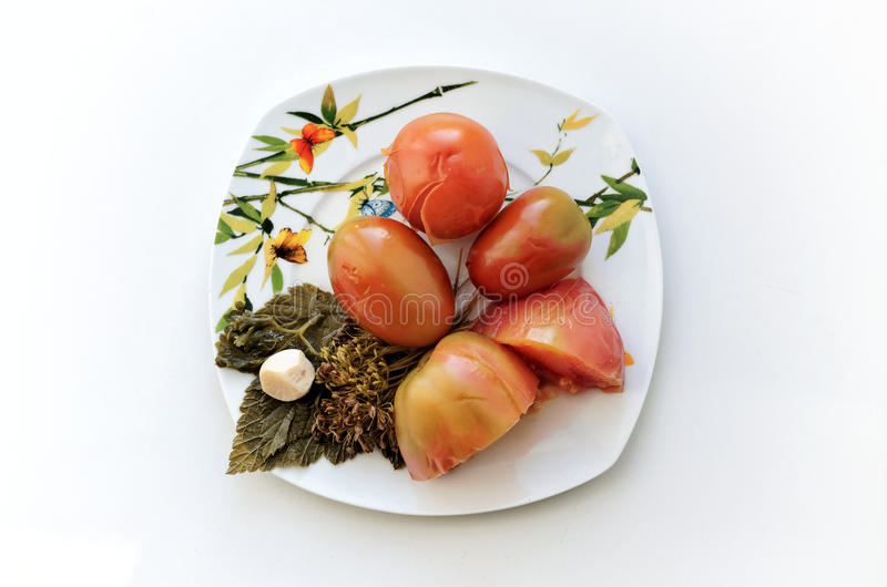 Pickled tomatoes with leaves of currant on a plate. Top view royalty free stock photos