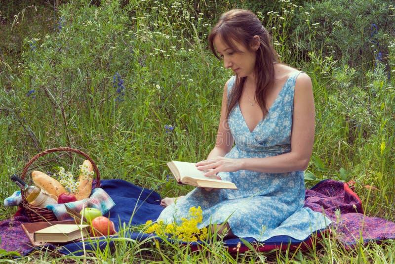 Picknick in aard bij de zomer Jonge vrouw in romantische blauwe kleding i stock foto's