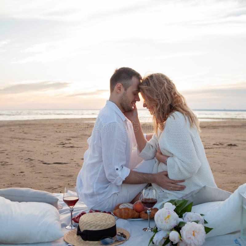 Picknick bij zonsondergang De man en een zwangere vrouw zitten op een sprei, op het strand, koesteren, die tegen eb kussen stock foto's