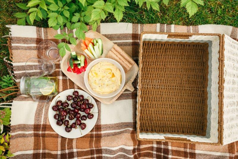 Picknick buiten in het Park op de gras rieten doos, geruite pl stock fotografie