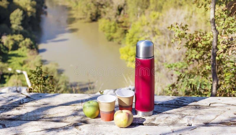 Picknick in de hoge berg met rode thermosflessen, koffie en appelen stock foto's