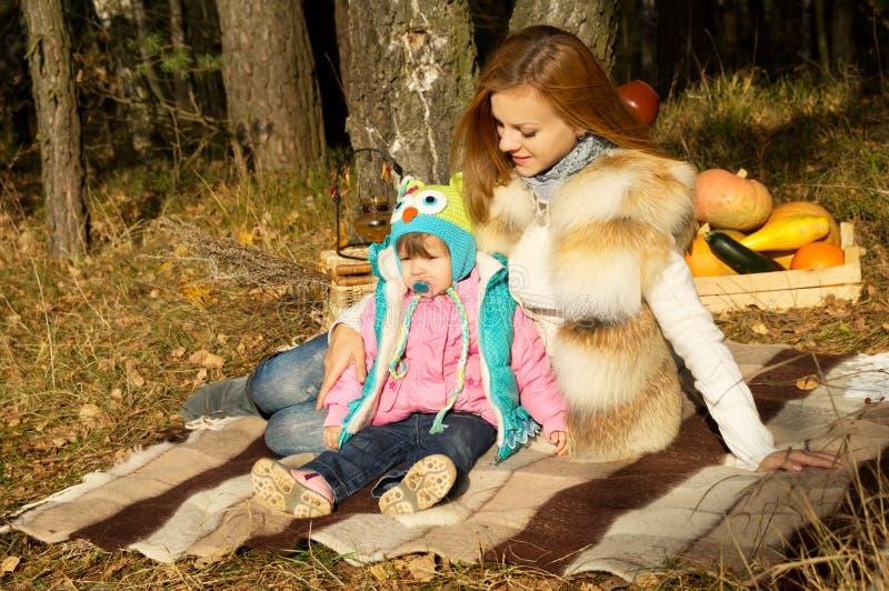 Picknick, die Mutter und Tochter, die im Herbst stillstehen stockfotografie