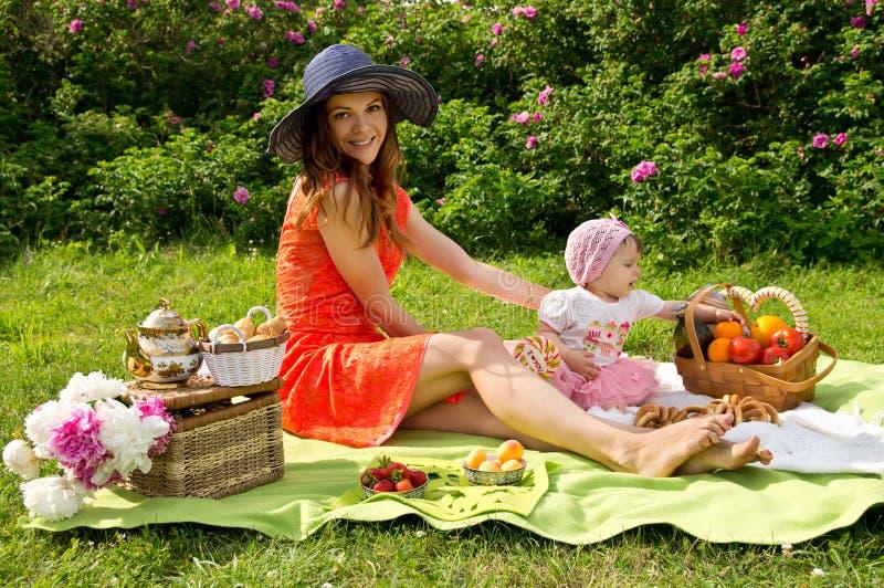 Picknick, een jonge moeder met haar dochter stock fotografie