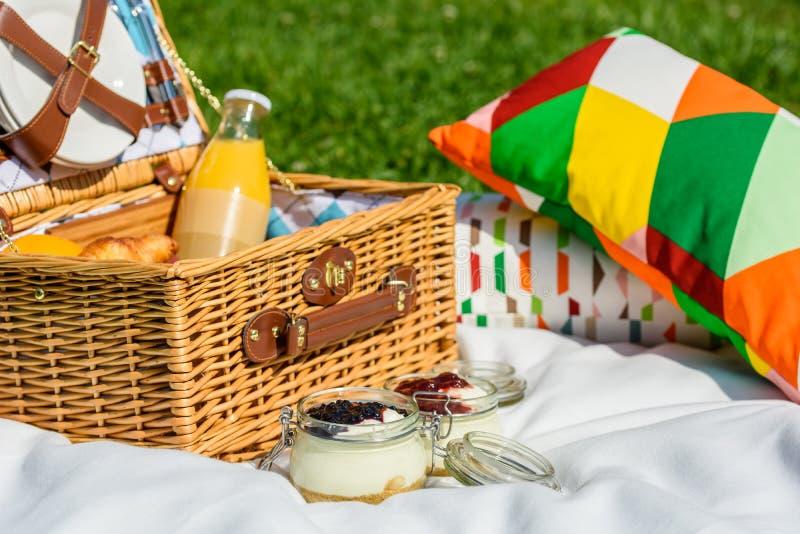 Picknick-Korb mit Früchten, Orangensaft, Hörnchen und kein backen Blaubeer-und Erdbeerkäsekuchen lizenzfreie stockfotos