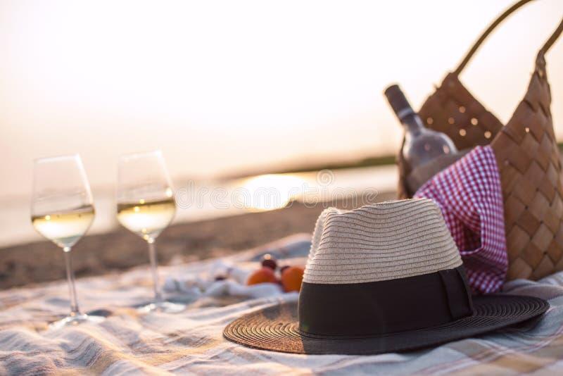 Picknick met wijn op het strand door het overzees Romantisch diner bij zonsondergang De ruimte van het exemplaar royalty-vrije stock foto