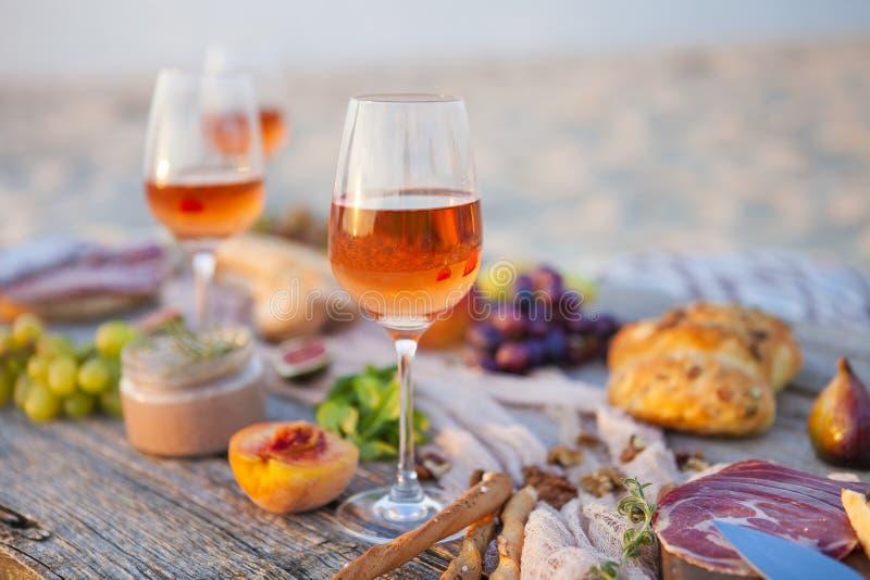 Picknick op het strand bij zonsondergang in conc bohostijl, voedsel en drank stock foto's