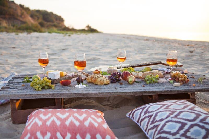Picknick op het strand bij zonsondergang in conc bohostijl, voedsel en drank stock fotografie