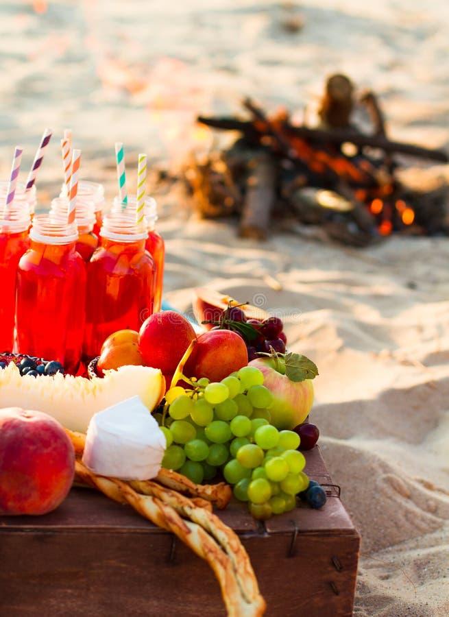 Picknick op het strand bij zonsondergang in de bohostijl stock afbeeldingen