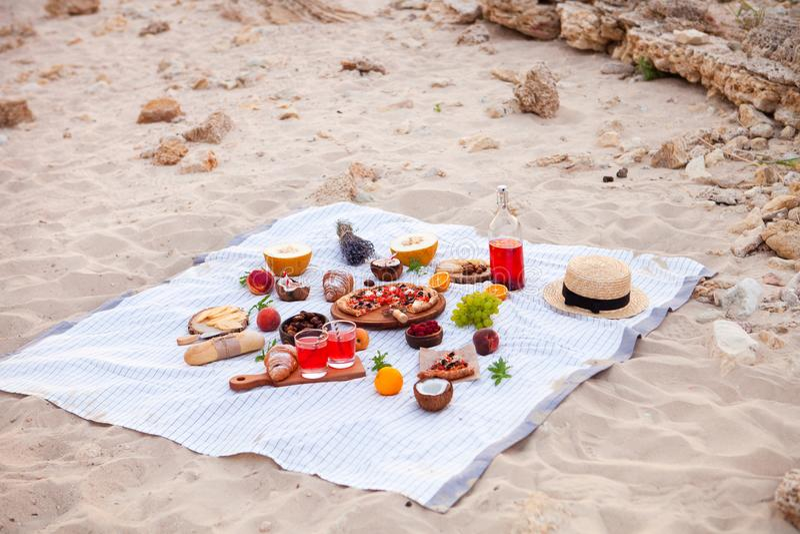 Picknick op het strand bij zonsondergang in de witte plaid, het voedsel en de drank stock foto's