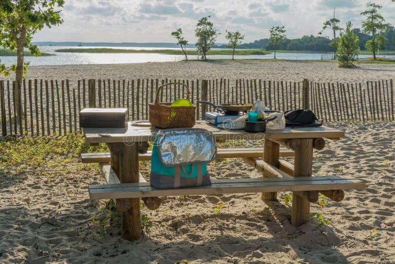 Picknick op het strand bij zonsondergang, voedsel en drankconceptie stock foto
