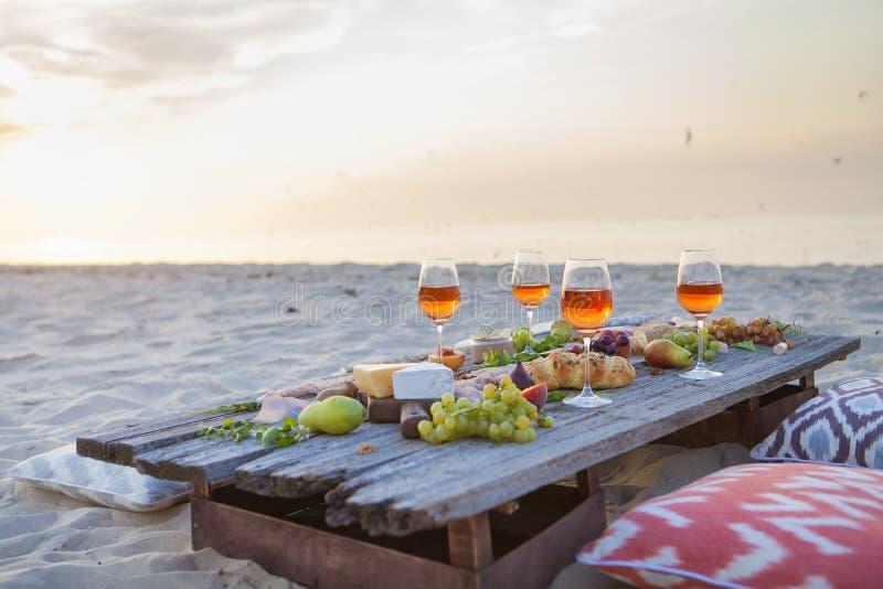 Picknick på stranden på solnedgången i den conc bohostil, mat och drinken royaltyfri fotografi