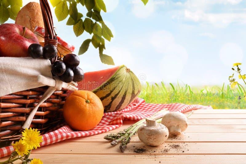 Picknick rieten mand met voedsel op de gebieds blauwe achtergrond stock foto