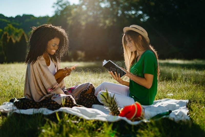 Picknick von zwei Multirennfreundinnen Das reizende junge blonde Mädchen liest das Buch während ihr glücklicher lächelnder Afrika lizenzfreie stockfotos