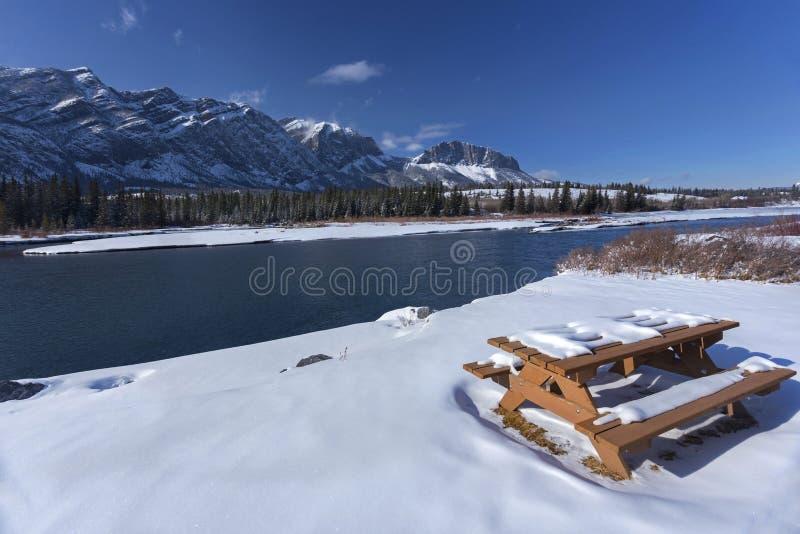 Picknickbänk som täckas av snö vid pilbågefloden i Alberta Foothills Canadian Rockies arkivbilder