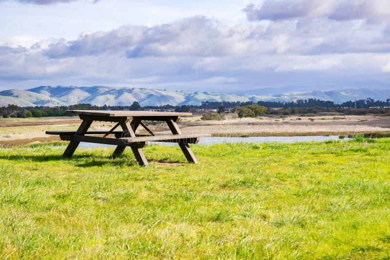 Picknickbank dichtbij een vijver, bergachtergrond, het Regionale park van Coyoteheuvels, baaigebied de Oost- van San Francisco, C royalty-vrije stock afbeelding